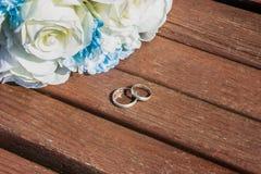 Искусственный букет белых роз и 2 кольца на стенде стоковые изображения
