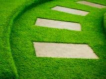 Искусственный путь прогулки зеленой травы с конкретной плитой Стоковая Фотография RF