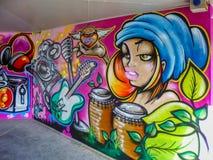 Искусство стены граффити настенной росписи девушки музыканта с барабанчиком и гитарой конго стоковая фотография rf
