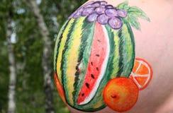 Искусство тела оранжевых плодоовощ и ягод арбуза и виноградин на теле беременной женщины на естественной предпосылке Стоковое Изображение