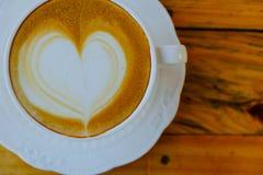 Искусство latte кофе на деревянной чашке таблицы Стоковое фото RF