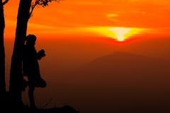 Искусство silhouettes чтение женщины на sunsetIn предпосылка Mou Стоковая Фотография