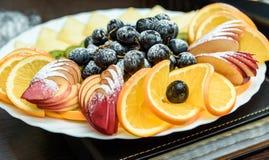 диск плодоовощ красиво отрезанных апельсинов, яблок, персиков, кивиа и виноградин близко вверх Стоковые Изображения
