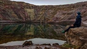 Исландия - человек сидя на утесе небольшим озером стоковое фото