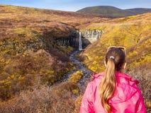 Исландия - backwords девушки стоя и восхищать водопад перед ей стоковые изображения rf