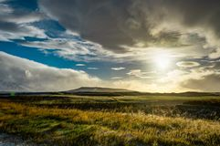 Исландский ландшафт с голубым небом и солнцем и облаками с mounta Стоковые Фото