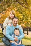 Испанец смешанной гонки и портрет кавказской семьи внешний на парке стоковая фотография