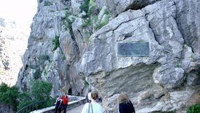 ИСПАНИЯ, БАРСЕЛОНА 13-ОЕ АПРЕЛЯ 2019: Пешая тропа с пещерами на ноге утесов r Туристы наслаждаются красивой прогулкой горы видеоматериал