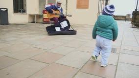 Испания ronda 9-ое января 2017 Радостный ребенк танцует и бежит в историческом месте Музыкант улицы играя гитару сток-видео