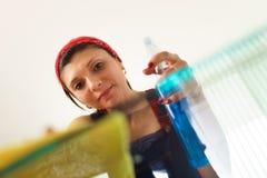 Испанская горничная девушки дома делая работы по дому очищая стеклянный стол Стоковое Фото