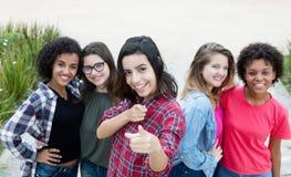 Испанская женщина показывая большой палец руки с группой в составе подруги Стоковое Изображение RF