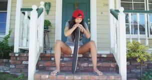 Испанская женщина сидя на крылечке с скейтбордом Стоковое Фото