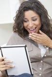 Испанская женщина смеясь над используя компьютер таблетки Стоковая Фотография RF