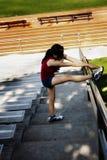 Испанская предназначенная для подростков женщина протягивая с ногой вверх на рельсе стоковые фотографии rf