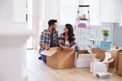 Испанские пары двигая в новый дом и распаковывая коробки Стоковая Фотография