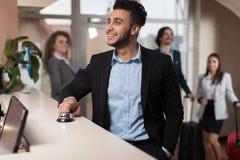 Испанский бизнесмен приезжает к гостинице ждать проверяет внутри бизнесменов группы регистрации в лобби стоковое изображение