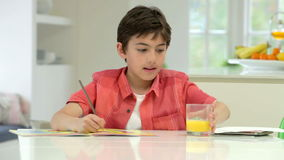 Испанский мальчик делая домашнюю работу на счетчике кухни видеоматериал