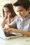 Испанский мальчик и девушка используя компьтер-книжку Стоковое Фото