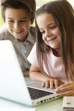 Испанский мальчик и девушка используя компьтер-книжку Стоковое Изображение