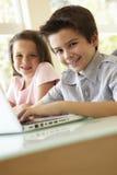 Испанский мальчик и девушка используя компьтер-книжку Стоковые Изображения RF