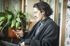 Испанский молодой человек используя smartphone сидя на террасе стоковая фотография