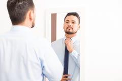 Испанский молодой человек надевая галстук Стоковые Фотографии RF