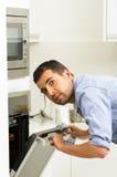 Испанский мужчина нося голубую рубашку в современной кухне Стоковые Фото