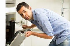 Испанский мужчина нося голубую рубашку в современной кухне Стоковые Изображения RF
