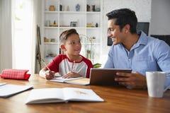 Испанский пре-предназначенный для подростков мальчик сидя на таблице работая с его домашним гувернером школы, усмехаясь на одине  стоковое изображение
