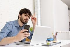 Испанский привлекательный бизнесмен битника работая дома офис используя мобильный телефон Стоковое Изображение RF