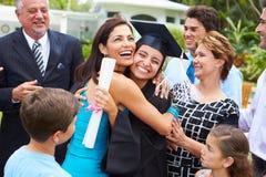 Испанский студент и семья празднуя градацию
