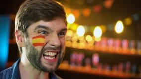 Испанский футбольный болельщик с флагом на щеке веселя для турнира команды выигрывая видеоматериал