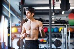 Испанский человек в спортзале отдыхая, держащ наушники, слушая музыка Стоковые Изображения RF