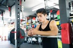 Испанский человек в спортзале отдыхая, держащ умный телефон, слушая музыка Стоковое фото RF