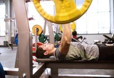 Испанский человек в спортзале разрабатывая с весами, отжимать стенда Стоковое Изображение