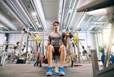 Испанский человек в спортзале сидя на стенде, разрабатывая с весами Стоковое Изображение