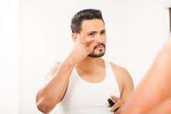 Испанский человек используя нижнюю сливк глаза Стоковое фото RF