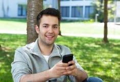 Испанский человек снаружи в парке посылая сообщение Стоковые Изображения