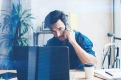 Испанский элегантный бизнесмен работая современная тетрадь пока сидящ на деревянном столе на солнечном офисе Говорить человека Стоковые Изображения RF