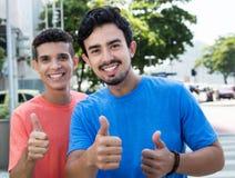 2 испанских парня показывая большие пальцы руки в городе Стоковая Фотография RF