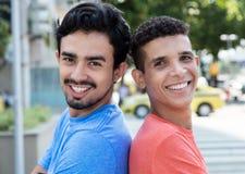 2 испанских парня спина к спине в городе Стоковое Фото