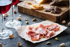 Испанское serrano jamon ветчины или итальянское crudo ветчины с отрезанным итальянским трудным сыром, домодельным высушенным саля Стоковые Фото