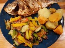 испаренный n зажарил в духовке Dorado со сладкими картофелями и овощами стоковая фотография