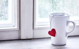 Испаряющся чай утра сердца влюбленности mug на силле окна стоковые изображения rf