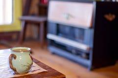 Испаряющся чашка кофе в кружке птицы с винтажным обогревателем кабины пропана/природного газа на заднем плане - принятый на дерев стоковое фото