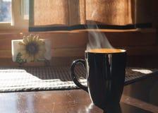 Испаряясь кружка горячего питья на деревенском деревянном столе стоковое изображение