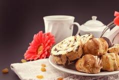 Испеките крен и eclair на плите с кофе на темной предпосылке Стоковая Фотография