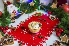 Испеките, стоящ на красной салфетке рождества на белом деревянном столе окруженном зеленой гирляндой и светами рождества Стоковая Фотография RF