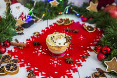 Испеките, стоящ на красной салфетке рождества на белом деревянном столе окруженном зеленой гирляндой и светами рождества Стоковые Изображения
