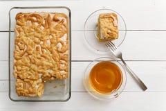Испеките с завалкой и меренгой лимон-апельсина около чашки чаю Стоковая Фотография